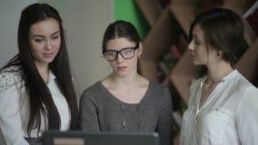 La ragazza indica sullo schermo del computer portatile dalla sua mano archivi video
