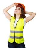 La ragazza indossa un casco del costruttore della maglia sulla sua testa Isolato Immagini Stock