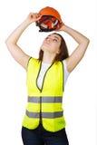 La ragazza indossa un casco del costruttore della maglia sulla sua testa Isolato Immagini Stock Libere da Diritti
