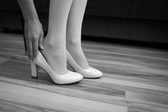 La ragazza indossa una scarpa sulla gamba La sposa mette le sue scarpe di mattina nell'interno immagini stock