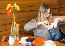 La ragazza infelice non può trovare qualcosa nella sua borsa Fotografie Stock Libere da Diritti