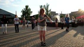 La ragazza insegna alla gente a come ballare la salsa, al tramonto sul quadrato stock footage