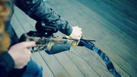 La ragazza inserisce la freccia nella balestra