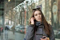 La ragazza inserisce il ricevitore telefonico nel suo orecchio Immagini Stock