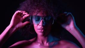 La ragazza insolita di fascino con i capelli ricci di afro corregge i suoi vetri Donna sexy con trucco perfetto che esamina macch archivi video