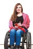 La ragazza invalida della donna sulla sedia a rotelle tiene la tazza del tè immagine stock