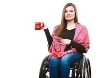 La ragazza invalida della donna sulla sedia a rotelle tiene la tazza del tè immagine stock libera da diritti
