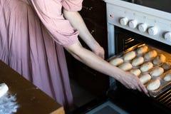 La ragazza invia con le torte nel forno La donna cucina le torte tradizionali immagini stock