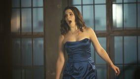 la ragazza 4k in un vestito blu da sera lussuosa che fila intorno, balla e canta stock footage