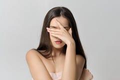 La ragazza la copre occhi di sua mano fotografia stock