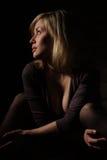 La ragazza la seduta bionda ad una parete. fotografia stock libera da diritti