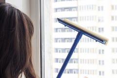 La ragazza lava la finestra, primo piano fotografia stock libera da diritti
