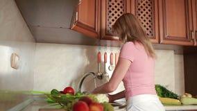 La ragazza lava l'uva Verdure sul tavolo da cucina archivi video