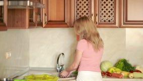 La ragazza lava l'uva Verdure sul tavolo da cucina Pomodori e cavolo stock footage