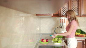La ragazza lava l'uva Verdure sul tavolo da cucina Pomodori e cavolo archivi video
