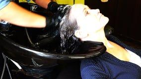 La ragazza lava la sua testa prima della procedura nel salone di bellezza stock footage