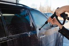 La ragazza lava SUV nero con un autolavaggio ad alta pressione Schiuma ed acqua del sapone sulla macchina Autolavaggio di self se fotografia stock libera da diritti