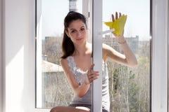 La ragazza lava una finestra Immagini Stock