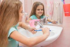 La ragazza lava uno spazzolino da denti sotto il rubinetto Fotografia Stock