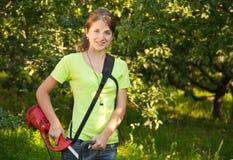 La ragazza lavora con la erba-taglierina Fotografie Stock
