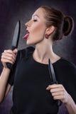 La ragazza lecca il coltello. Immagine Stock Libera da Diritti