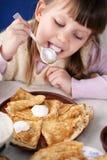 La ragazza lecca il cucchiaio Fotografia Stock