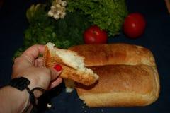 La ragazza lega fuori il pane fresco con le verdure fotografie stock
