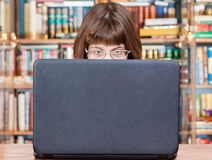 La ragazza legge dallo schermo del computer portatile in biblioteca Immagini Stock