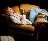 La ragazza legge i libri in una poltrona fotografia stock libera da diritti