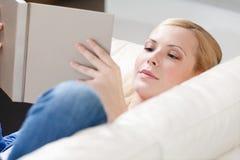 La ragazza legge il libro che si trova sul sofà Fotografia Stock Libera da Diritti
