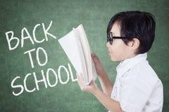 La ragazza legge il libro con testo di nuovo alla scuola Immagine Stock Libera da Diritti