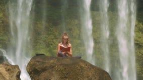 La ragazza legge il libro contro le piante dietro i getti della cascata video d archivio