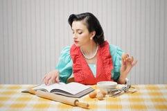 La ragazza legge un libro di cucina immagini stock