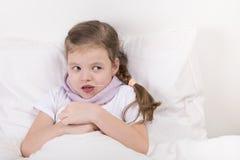 La ragazza a letto, ha preso una cucchiaiata di medicina e degli sguardi alla destra Immagini Stock Libere da Diritti