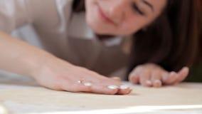 La ragazza liscia la pasta con le sue mani sulla tavola, assicurandosi che sia anche archivi video