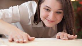 La ragazza liscia la pasta con le sue mani sulla tavola, assicurandosi che sia anche video d archivio