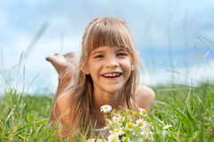 La ragazza llaughing sta trovandosi sull'erba Fotografie Stock Libere da Diritti