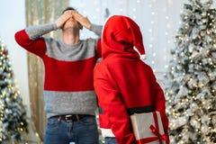 La ragazza in maglione di Santa si prepara per dare un regalo ed il tipo sta aspettando coprendo i suoi occhi di sue mani immagine stock