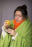 La ragazza malata di influenza preme un limone nel vostro tè Fotografia Stock