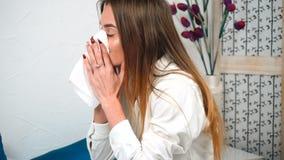 La ragazza malata starnutisce in fazzoletto a casa stock footage