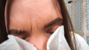 La ragazza malata starnutisce nella casa del fazzoletto video d archivio