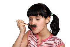 La ragazza mangia con il cucchiaio Immagine Stock