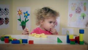 La ragazza mangia i cerchi deliziosi del cereale sulla sua tavola della stanza stock footage
