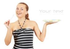 La ragazza mangia i piselli in scatola da una spina Fotografie Stock Libere da Diritti