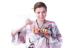 La ragazza mangia i sushi Fotografia Stock Libera da Diritti