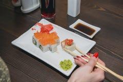 La ragazza mangia i sushi, i bastoni del giapponese al ristorante giapponese Immagini Stock Libere da Diritti
