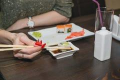 La ragazza mangia i sushi, i bastoni del giapponese al ristorante giapponese Immagine Stock