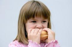 La ragazza mangia il pane Fotografia Stock