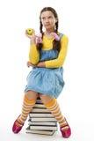 La ragazza mangia la mela che si siede sul mucchio dei libri Fotografia Stock