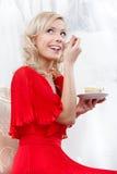 La ragazza mangia la torta nunziale Fotografia Stock